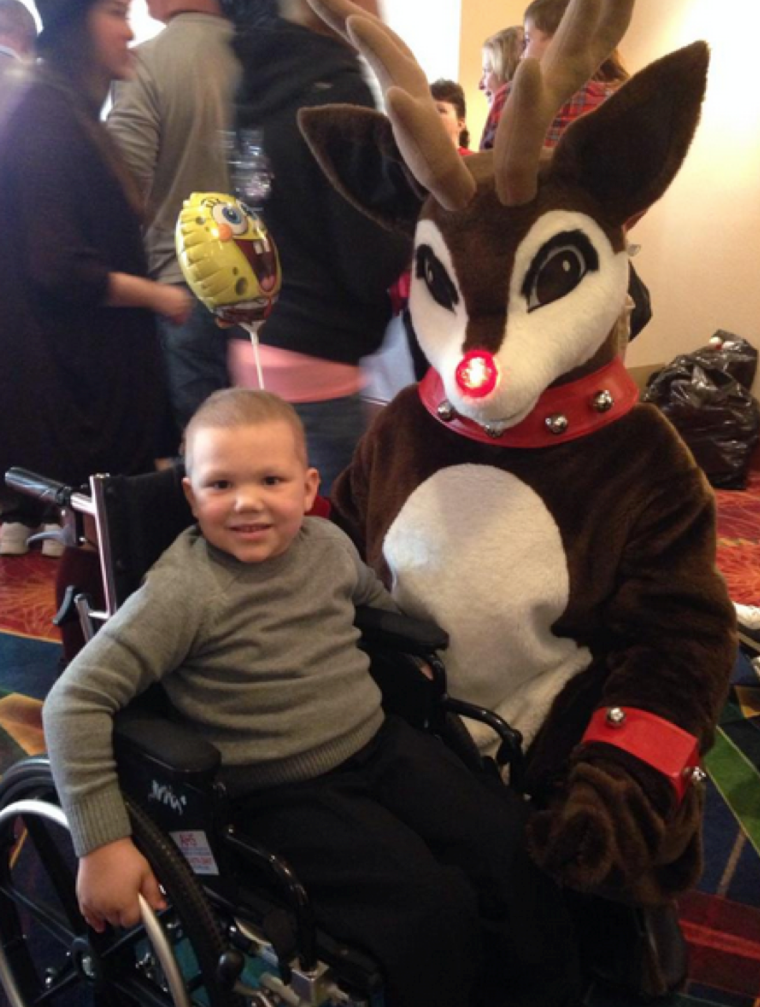 "Thomas (more commonly known as ""Super-hero Thomas"") spends time with Rudolph the Red-Nosed Reindeer at the Jimmy Fund Clinic Winter Festival."