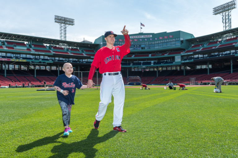 Brock Holt leads Layla across the Fenway Park outfield to show her the iconic Green Monster.